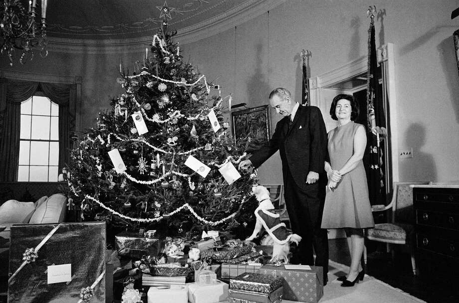 President Lyndon Johnson and Lady Bird Johnson, and Yuki, the White House pet, pose beside the family Christmas tree in Washington, Dec. 24, 1967, a Norway spruce. Yuki takes a stand atop some of the family Christmas gifts arranged under the tree. The President returned from his round-the-world journey. The setting is in the Yellow Oval Room in the second floor of the White House. Photo: Anonymous, Associated Press / AP1967
