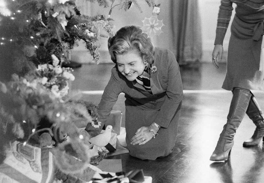 First lady Betty Ford looks over decorations and presents under the White House Christmas Tree in Washington in the Blue Room of the presidential mansion in Washington.  In 1974 Betty Ford went with a patchwork-trimmed tree, and distributed instructions so families around the country could make their own decorations. Photo: Charles Tasnadi, Associated Press / AP1976