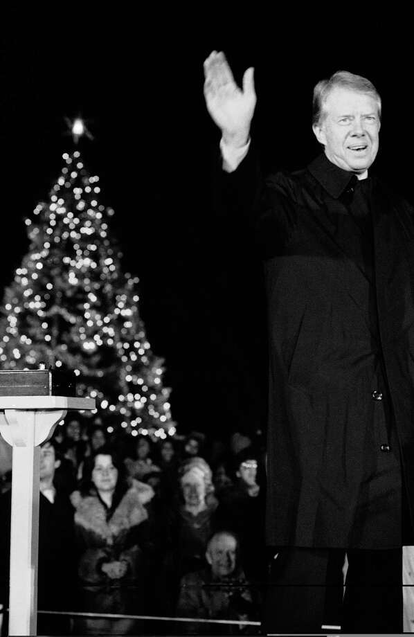 President Jimmy Carter waves after he and his daughter Amy pressed the button that turned on the lights of the National Christmas Tree on the Ellipse in Washington on Thursday, Dec. 15, 1978. The tree has been traditionally lighted by the President of the United States since 1923, when President Calvin Coolidge did the honors. Photo: Associated Press