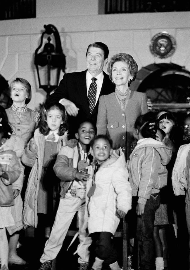 President Ronald Reagan, back center, and Mrs. Ronald Reagan, surrounded by students from Martin Luther King Elementary school, look toward the National Christmas Tree after pushing the switch to light the tree, Thursday, Dec. 13, 1984, Washington, D.C. The tree, on the Ellipse, is a living 30-foot Colorado Blue Spruce decorated with 1,600 translucent green lights. The rest of the group is unidentified. Photo: Ira Schwarz, Associated Press / AP1984