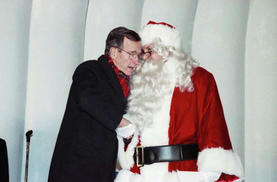 U.S. President George H. Bush shakes hand with Santa Claus, being portrayed by television personality Williard Scott, while lighting the National Christmas Tree on the Ellipse of the White House in Washington, Thursday, Dec. 14, 1989. Photo: Doug Mills, Associated Press / AP1989