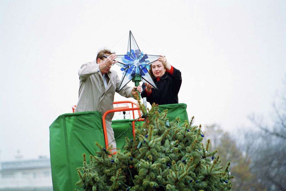 First lady Hillary Rodham Clinton, with the help of John Betchkal, president of the Christmas Pageant of Peace, places a stained glass ornament atop the National Christmas tree in Washington, Nov. 28, 1994. The first lady took a hydraulic lift to the top of the tree, which President Clinton is expected to light up during the 1994 Pageant of Peace on December 7. Photo: Associated Press
