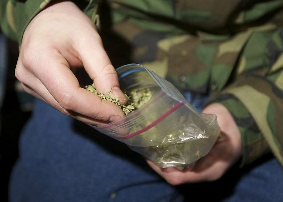 A Seattle resident takes marijuana from a plastic bag shortly after a law legalizing the recreational use of  marijuana took effect on December 6, 2012 in Seattle, Washington.  Voters approved an initiative to decriminalize the recreational use of marijuana making it one of the first states to do so. Photo: Stephen Brashear, Getty Images