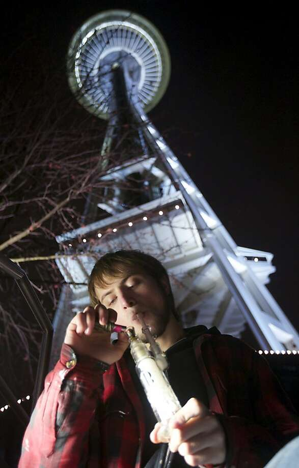 Paul of Tacoma, who wouldn't give his last name, inhaled a lungful of newly legalized pot from a water pipe underneath Seattle's Space Needle. Photo: Stephen Brashear, Getty Images