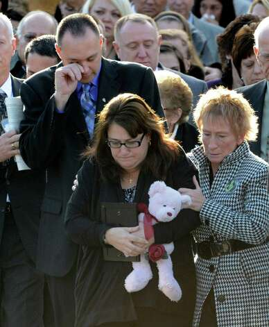 Brian, left, and Deborah Rivers, with teddy bear, cry for their late daughter Deanna Rivers, following funeral services at St. Edward the Confessor Church in Clifton Park, N.Y. Dec 6, 2012. Rivers died Saturday night in car accident which also claimed the life of fellow Shenendehowa student Christopher Stewart. (Skip Dickstein/Times Union) Photo: SKIP DICKSTEIN / 00020374A