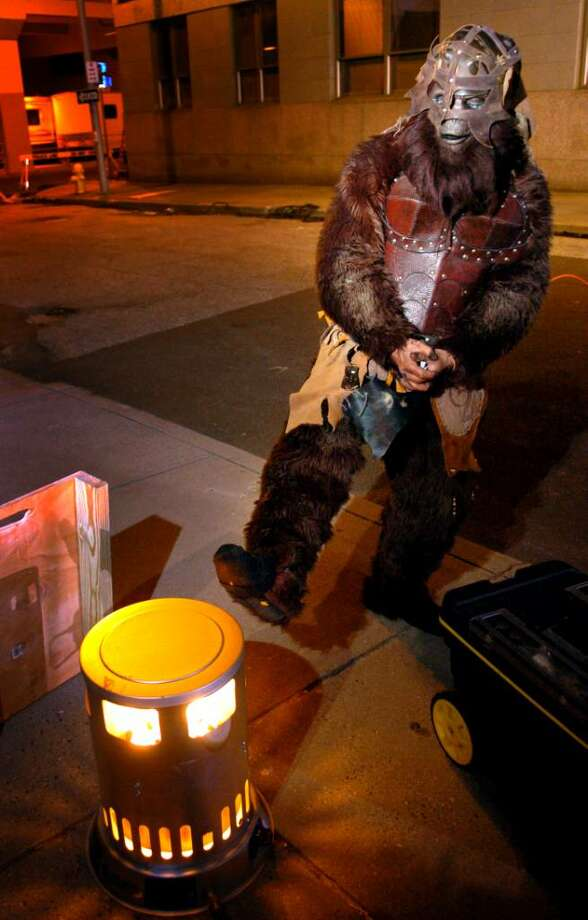 "A monkey from ""The Witches of Oz"" warms his feet between takes Thursday evening in downtown Bridgeport. Photo: Autumn Driscoll / Connecticut Post"
