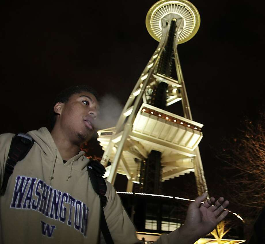 Andre Edwards smokes marijuana, Thursday, Dec. 6, 2012, just after midnight at the Space Needle in Seattle. Possession of marijuana became legal in Washington state at midnight, and several hundred people gathered at the Space Needle to smoke and celebrate the occasion, even though the new law does prohibit public use of marijuana. Photo: Ted S. Warren, Associated Press