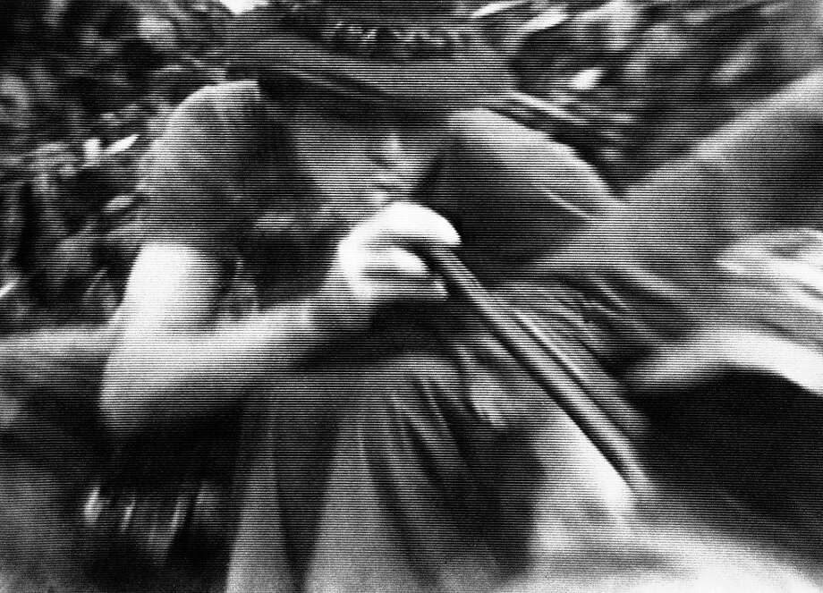 "In this file still image made from Nov. 13, 1970, video, soldiers in fire support base Aries, a small clearing in the jungles of War Zone D, 50 miles from Saigon, smoke marijuana using the barrel of a shotgun they nicknamed ""Ralph"" to get high. Photo: Jim Wells, Associated Press"