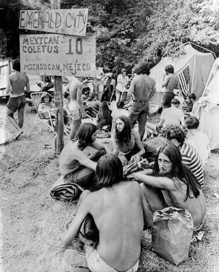 "In this Aug. 1, 1970, file photo, youths sell marijuana openly from sacks at a banned music festival in Middlefield, Conn. beneath a sign advertising their products as ""Mexican Coletus at $10 an ounce.""As the conformity of the postwar era took hold, getting high on marijuana and other drugs emerged as a symbol of the counterculture, with Jack Kerouac and the rest of the Beat Generation singing pot's praises. Photo: Anonymous, Associated Press"