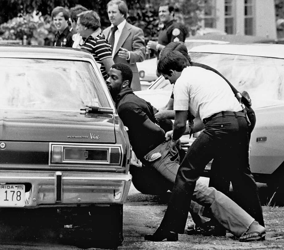 In this May 18, 1979 file photo, police handcuff a suspect during a drug raid in Miami. Police said eight were arrested and marijuana was seized. Photo: Al Diaz, Associated Press