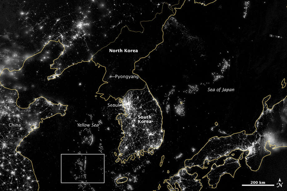 In this image from Sept. 24, 2012 provided by NASA, the Korean Peninsula is seen at night from a composite assembled from data acquired by the Suomi NPP satellite. The image was made possible by the new satellite�s �day-night band� of the Visible Infrared Imaging Radiometer Suite (VIIRS), which detects light in a range of wavelengths from green to near-infrared and uses filtering techniques to observe dim signals such as city lights, gas flares, auroras, wildfires, and reflected moonlight.  City lights at night are a fairly reliable indicator of where people live. But this isn�t always the case, and the Korean Peninsula shows why. As of July 2012, South Korea�s population was estimated at roughly 49 million people, and North Korea�s population was estimated at about half that number. But where South Korea is gleaming with city lights, North Korea has hardly any lights at all, just a faint glimmer around Pyongyang. The wide-area image shows the Korean Peninsula, parts of China and Japan, the Yellow Sea, and the Sea of Japan. The white inset box encloses an area showing ship lights in the Yellow Sea. Many of the ships form a line, as if assembling along a watery border. (AP Photo/NASA) Photo: Earth