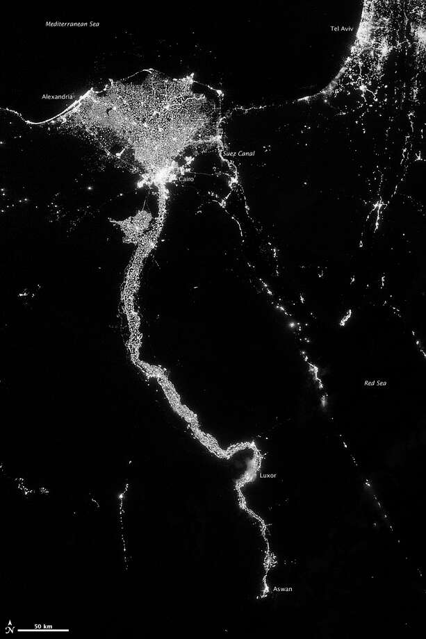In this image from Oct. 13, 2012 provided by NASA, the Nile River valley and delta is seen at night from a composite assembled from data acquired by the Suomi NPP satellite. The image was made possible by the new satellite�s �day-night band� of the Visible Infrared Imaging Radiometer Suite (VIIRS), which detects light in a range of wavelengths from green to near-infrared and uses filtering techniques to observe dim signals such as city lights, gas flares, auroras, wildfires, and reflected moonlight. The Nile River Valley and Delta comprise less than 5 percent of Egypt�s land area, but provide a home to roughly 97 percent of the country�s population. Nothing makes the location of human population clearer than the lights illuminating the valley and delta at night. The city lights resemble a giant calla lily, just one with a kink in its stem near the city of Luxor. Some of the brightest lights occur around Cairo, but lights are abundant along the length of the river. Bright city lights also occur along the Suez Canal and around Tel Aviv. Away from the lights, however, land and water appear uniformly black. This image was acquired near the time of the new Moon, and little moonlight was available to brighten land and water surfaces. (AP Photo/NASA) Photo: Earth