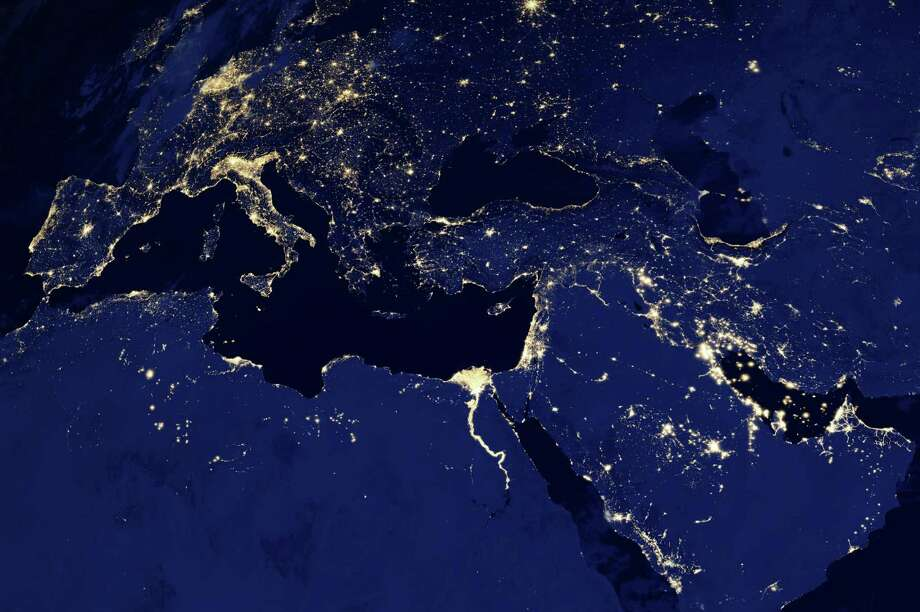"This NASA  image obtained December 6, 2012 shows a new global view of Earth's city lights  in part of Europe and North Africa and the Middle East at night in a composite assembled from data acquired by the Suomi National Polar-orbiting Partnership (Suomi NPP) satellite. The data was acquired over nine days in April 2012 and thirteen days in October 2012. It took satellite 312 orbits and 2.5 terabytes of data to get a clear shot of every parcel of Earth's land surface and islands. This new data was then mapped over existing Blue Marble imagery to provide a realistic view of the planet.The image was made possible by the satellite's ""day-night band"" of the Visible Infrared Imaging Radiometer Suite (VIIRS), which detects light in a range of wavelengths from green to near-infrared and uses filtering techniques to observe dim signals such as city lights, gas flares, auroras, wildfires and reflected moonlight. = RESTRICTED TO EDITORIAL USE - MANDATORY CREDIT "" AFP PHOTO / NASA Earth Observatory/NOAA NGDC/"" - NO MARKETING NO ADVERTISING CAMPAIGNS - DISTRIBUTED AS A SERVICE TO CLIENTS =HO/AFP/Getty Images Photo: HO, AFP/Getty Images / AFP"