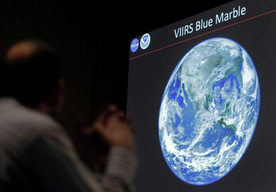 A man looks at a view of Earth from space during a media conference Wednesday, Dec. 5, 2012, at the American Geophysical Union meeting in San Francisco. The National Aeronautics and Space Administration has released new composite images of earth taken by the National Oceanic and Atmospheric Administration's Suomi National Polar-orbiting Partnership satellite. A new sensor aboard the NPP satellite is enabling scientists to observe Earth's atmosphere and surface during nighttime hours, in greater detail than ever before. Photo: Ben Margot, AP / AP