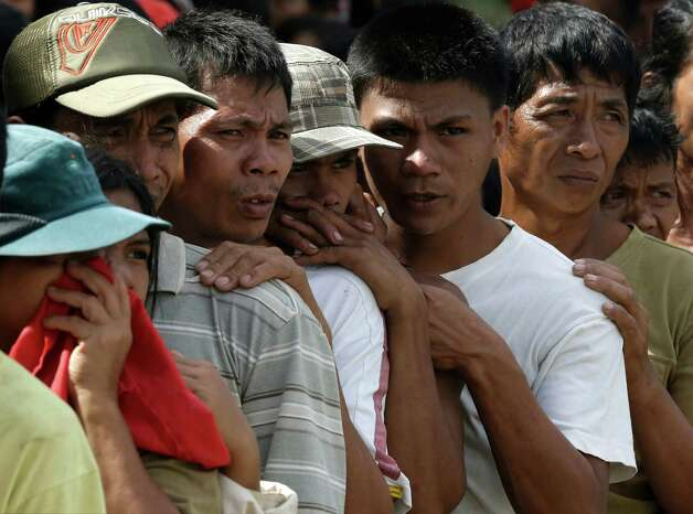 Residents, impacted by Tuesday's typhoon, line up for relief supplies at an evacuation center Thursday, Dec. 6, 2012, in New Bataan township, Compostela Valley in the southern Philippines.  The powerful typhoon that washed away emergency shelters, a military camp and possibly entire families in the southern Philippines has killed hundreds of people with nearly 400 missing, authorities said Thursday. Photo: Bullit Marquez, AP / AP