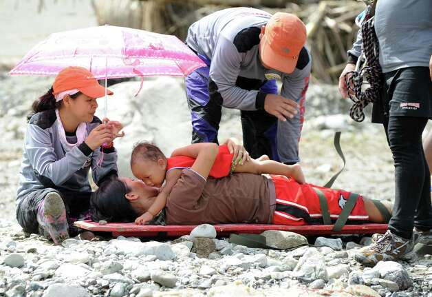 TOPSHOTS Lenlen Medrano and her child (on stretcher), survivors of Typhoon Bopha, prepare to be transported across a surging river on a zip line in the town of New Bataan, compostela province on December 6, 2012. Nearly 200,000 people are homeless and more than 300 dead after the Philippines suffered its worst typhoon this year, authorities said on December 6, reaching out for international aid to cope with the scale of the disaster.  AFP PHOTO / TED ALJIBETED ALJIBE/AFP/Getty Images Photo: TED ALJIBE, AFP/Getty Images / AFP