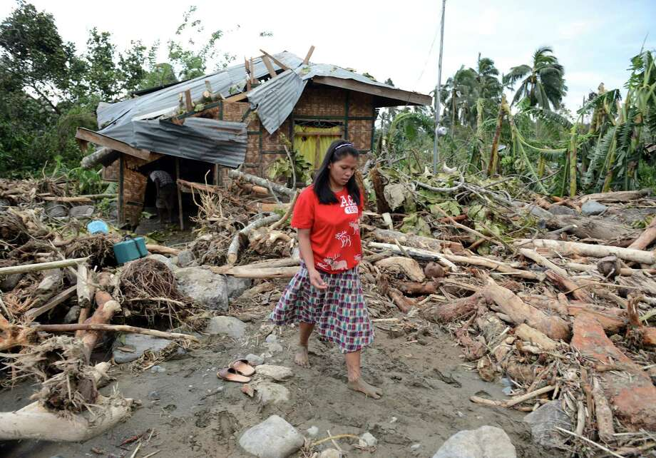 TOPSHOTS  A woman walks amongst debris next to her damaged house in the village of Andap, New Bataan town, Compostela Valley province on December 5, 2012, a day after Typhoon Bopha hit the province. At least 274 people have been killed and hundreds remain missing in the Philippines from the deadliest typhoon to hit the country this year, the civil defence chief said December 5.  AFP PHOTO/TED ALJIBETED ALJIBE/AFP/Getty Images Photo: TED ALJIBE, AFP/Getty Images / AFP