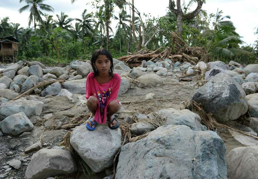 TOPSHOTS  A girl sits on top of boulders washed to the road by flash floods at the height Typhoon Bo