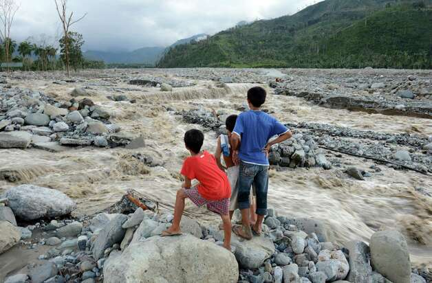 TOPSHOTS  Children look at the a damaged road destroyed by flash floods at the height of Typhoon Bopha in the village of Andap, New Bataan town, Compostela Valley province on December 5, 2012.  At least 274 people have been killed and hundreds remain missing in the Philippines from the deadliest typhoon to hit the country this year, the civil defence chief said December 5.  AFP PHOTO/TED ALJIBETED ALJIBE/AFP/Getty Images Photo: TED ALJIBE, AFP/Getty Images / AFP
