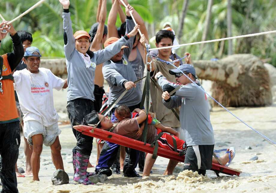 Lenlen Medrano and her child (on stretcher), survivors of Typhoon Bopha, are transported across a surging river on a zip line in the town of New Bataan, compostela province on December 6, 2012. Nearly 200,000 people are homeless and more than 300 dead after the Philippines suffered its worst typhoon this year, authorities said on December 6, reaching out for international aid to cope with the scale of the disaster.  AFP PHOTO / TED ALJIBETED ALJIBE/AFP/Getty Images Photo: TED ALJIBE, AFP/Getty Images / AFP