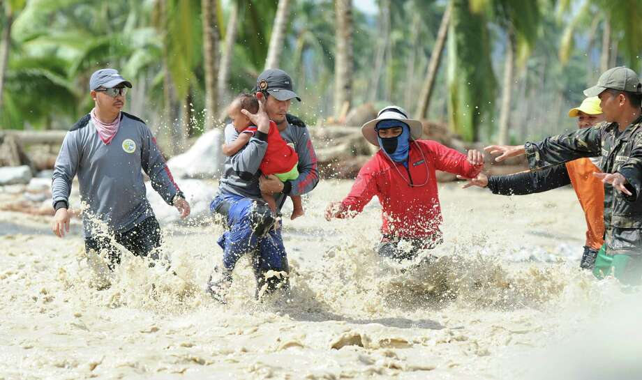 A rescue worker carries the child of Lenlen Medrino across a surging river in the town of New Bataan, compostela province on December 6, 2012. Nearly 200,000 people are homeless and more than 300 dead after the Philippines suffered its worst typhoon this year, authorities said on December 6, reaching out for international aid to cope with the scale of the disaster.  AFP PHOTO / TED ALJIBETED ALJIBE/AFP/Getty Images Photo: TED ALJIBE, AFP/Getty Images / AFP