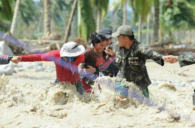 Lenlen Medrino (C) survivor of flash floods at the height of Typhoon Bopha, is helped by rescuers across a surging river in the town of New Bataan, compostela province on December 6, 2012. Nearly 200,000 people are homeless and more than 300 dead after the Philippines suffered its worst typhoon this year, authorities said on December 6, reaching out for international aid to cope with the scale of the disaster.  AFP PHOTO / TED ALJIBETED ALJIBE/AFP/Getty Images Photo: TED ALJIBE, AFP/Getty Images / AFP