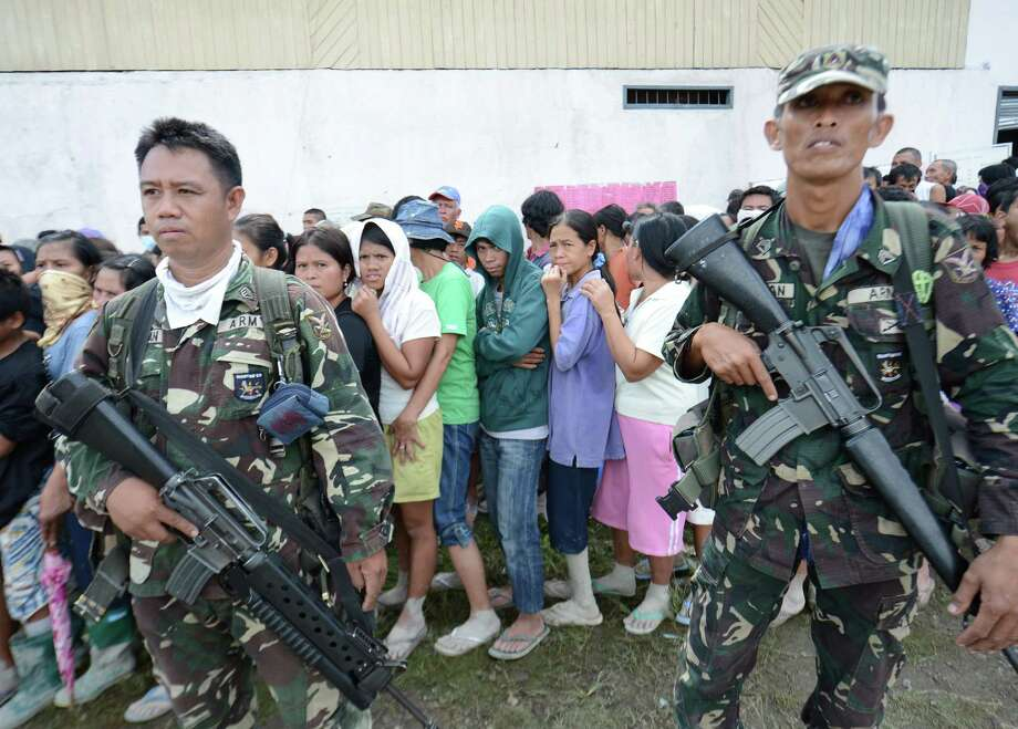 Philippine soldiers stand guard as residents queue up to receive food relief near the municipal hall in the town of New Bataan, compostela province on December 6, 2012. Nearly 200,000 people are homeless and more than 300 dead after the Philippines suffered its worst typhoon this year, authorities said on December 6, reaching out for international aid to cope with the scale of the disaster. AFP PHOTO / TED ALJIBETED ALJIBE/AFP/Getty Images Photo: TED ALJIBE, AFP/Getty Images / AFP