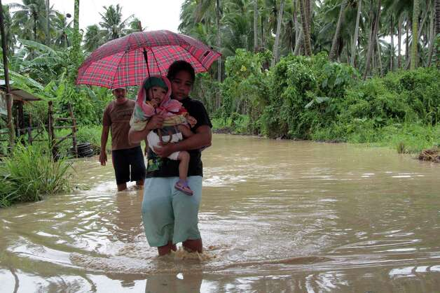 TOPSHOTS  A woman carrying her child wades through a flooded road brought about by heavy rains due to Typhoon Bopha, as she evacuates to a safer place, in Pantukan town, Compostela Valley province, in southern island of Mindanao on December 4, 2012. Typhoon Bopha killed 43 people in one hard-hit Philippine town December 4, local television station ABS-CBN reported from the scene.   AFP PHOTOSTR/AFP/Getty Images Photo: STR, AFP/Getty Images / cell:(63)9164168878             email:djcsantos@yahoo.com
