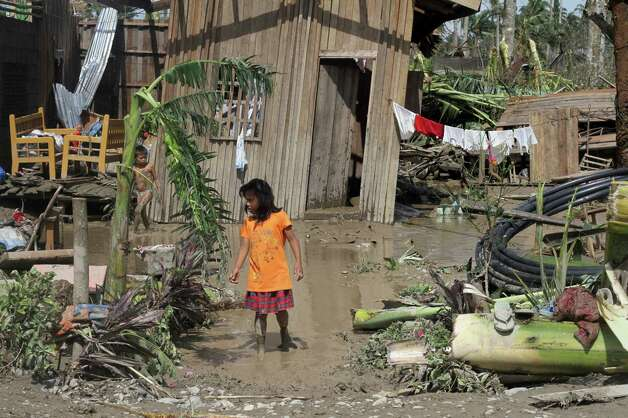 TOPSHOTS  Children walk in front of their flooded home in the aftermath of Typhoon Bopha in New Bataan, Compostela Valley in the southern Philippines on December 5, 2012. The death toll from a typhoon that ravaged the Philippines jumped to 238 on December 5 with hundreds missing, as rescuers battled to reach areas cut off by floods and mudslides, officials said. AFP PHOTO / Karlos ManlupigKARLOS MANLUPIG/AFP/Getty Images Photo: KARLOS MANLUPIG, AFP/Getty Images / AFP