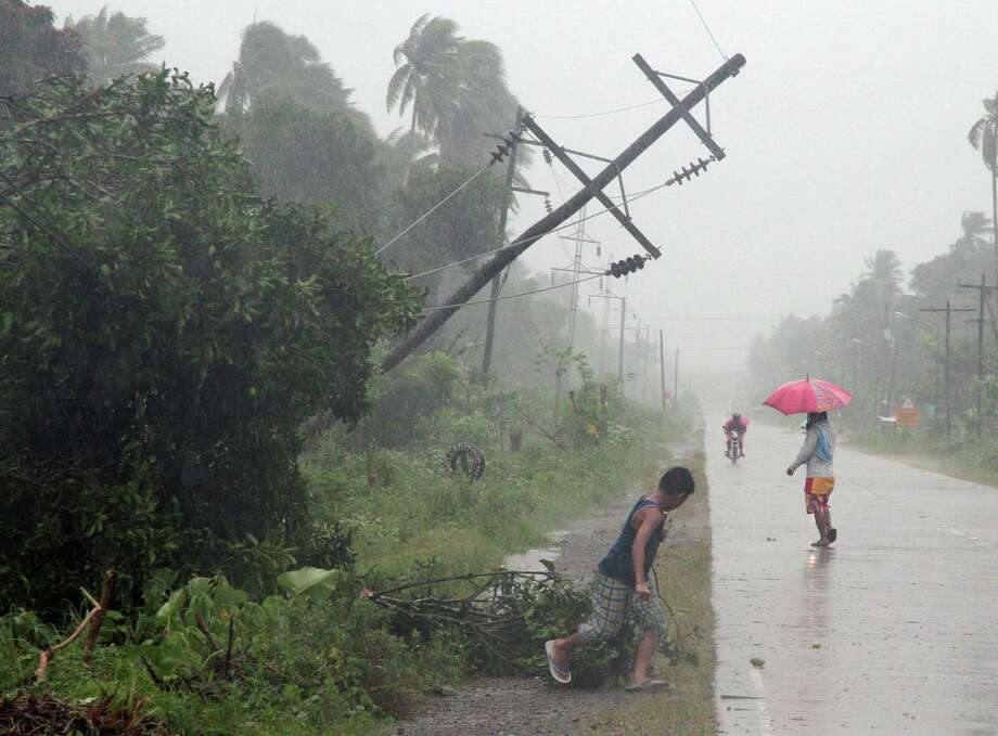 TOPSHOTS Residents brave heavy rains next to a tilted electric post after Typhoon Bophal hit the city of Tagum, Davao del Norter province, in southern island of Mindanao on December 4, 2012.  Typhoon Bopha smashed into the southern Philippines early December 4, as more than 40,000 people crammed into shelters to escape the onslaught of the strongest cyclone to hit the country this year.     AFP PHOTOSTR/AFP/Getty Images Photo: STR, AFP/Getty Images / AFP