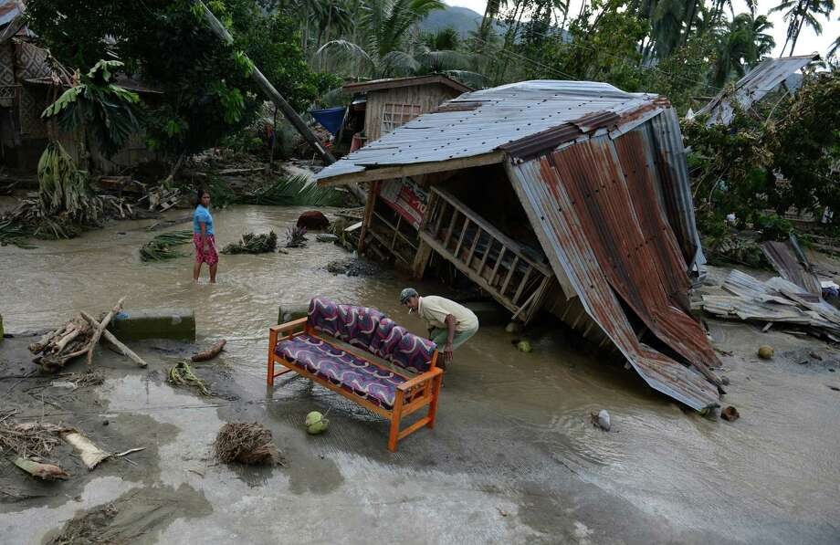 TOPSHOTS  Residents clean their sofa next to their damaged house in New Bataan town, Compostela Valley province on December 5, 2012, a day after Typhoon Bopha hit the province. At least 274 people have been killed and hundreds remain missing in the Philippines from the deadliest typhoon to hit the country this year, the civil defence chief said December 5.  AFP PHOTO/TED ALJIBETED ALJIBE/AFP/Getty Images Photo: TED ALJIBE, AFP/Getty Images / AFP