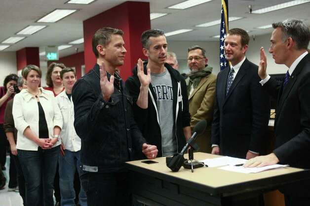 Same-sex advice columnist Dan Savage and his partner Terry Miller, left, take an oath that information provided is correct as they apply for their marriage license at the King County Administration Building on Thursday, December 6, 2012. Savage is a prominent gay rights activist. Photo: JOSHUA TRUJILLO / SEATTLEPI.COM
