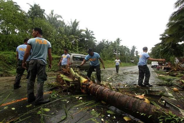 Philippine National Police clear a highway of toppled coconut trees after Typhoon Bopha made a landfall in Compostela Valley in southeastern Philippines Tuesday Dec. 4, 2012. A Philippine governor says at least 33 villagers and soldiers have drowned when torrents of water dumped by the powerful typhoon rushed down a mountain, engulfing the victims and bringing the death toll from the storm to about 40. Photo: Karlos Manlupig, AP / AP