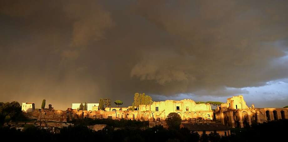 The sun breaks through a cloudy sky, illuminating ruins overlooking the Circus Maximus in Rome. Photo: Alberto Pizzoli, AFP/Getty Images
