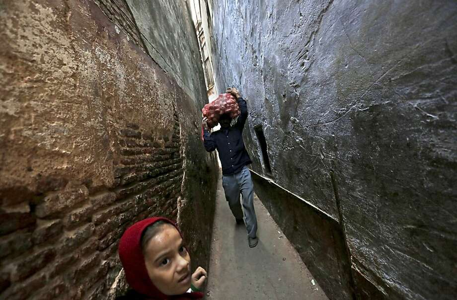 Tight squeeze: An Indian schoolgirl waits for a laborer to pass so his sack of potatoes won't get mashed in a very narrow alleyway in New Delhi. Photo: Kevin Frayer, Associated Press