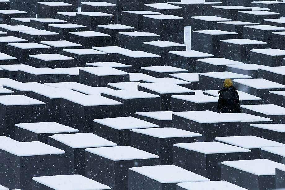 A visitor spends a quiet moment among the snow-covered slabs of the Holocaust Memorial in Berlin. Photo: Markus Schreiber, Associated Press