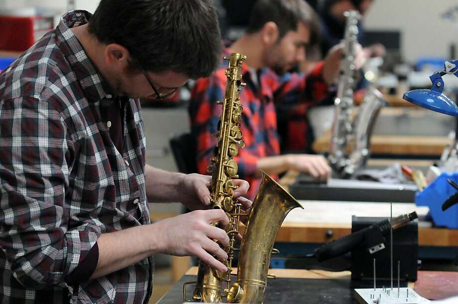 Sax therapy: MusicMedic.com repair technicians Ryan Walker (left) and Matt Hess work on saxophones at the company's workshop in Wilmington, N.C. Photo: Matt Born, Associated Press