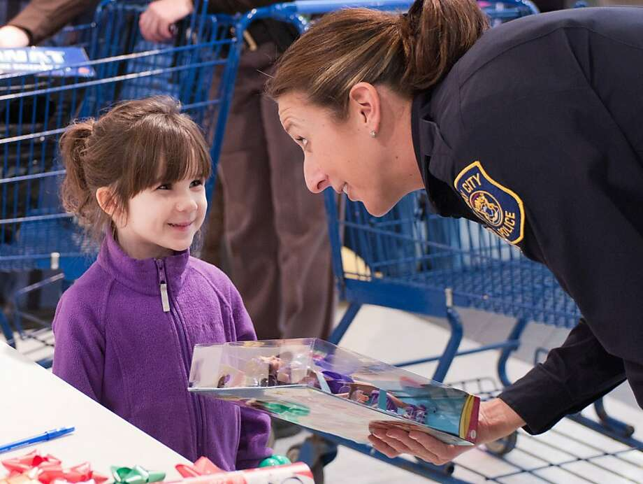 Her hero:Bay City Police Officer Leslie Darrow hands gifts to be wrapped to Kylee Lindner, 6, during Shop with a Hero day at a Meijer store in Monitor Township, Mich. Meijer paired Kylee and 31 other underprivileged children with Genesee County emergency responders for the event and gave each child a $100 gift card. Photo: Yfat Yossifor, Associated Press