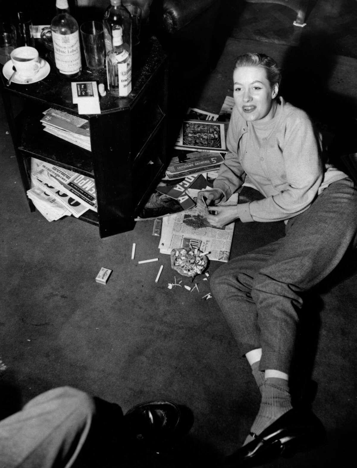 Commercial artist Christine Vasey rolls a marijuana reefer in 1950.