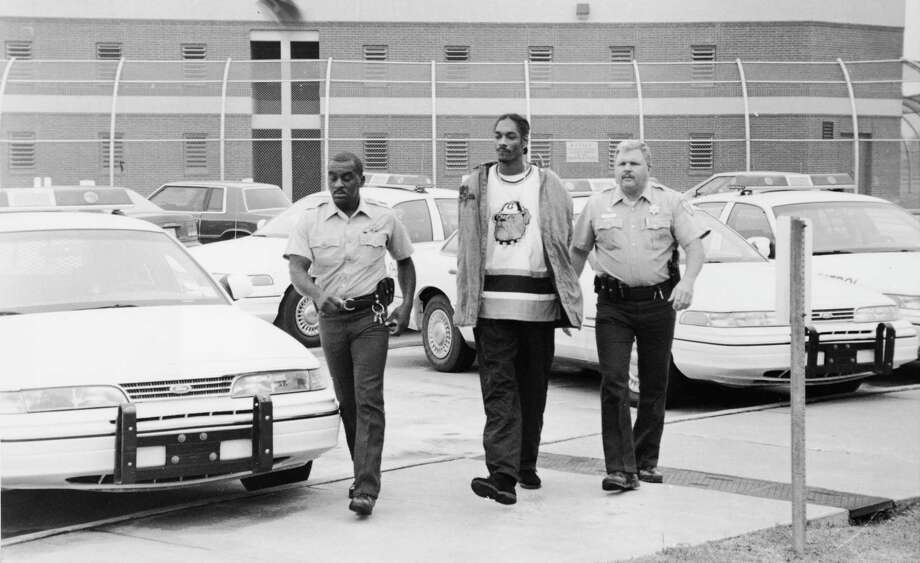 American rapper Snoop Dogg is escorted in handcuffs by two police officers following his arrest on charges of suspicion of possession of marijuana, circa 1995. Photo: Hulton Archive, Getty Images / 2003 Getty Images