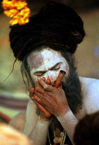 A Naga Sadhu (Hindu holy man) smokes marijuana at Kumbh in Allahabad, India on January 11, 2001.  Photo: DESHAKALYAN CHOWDHURY, AFP/Getty Images / AFP