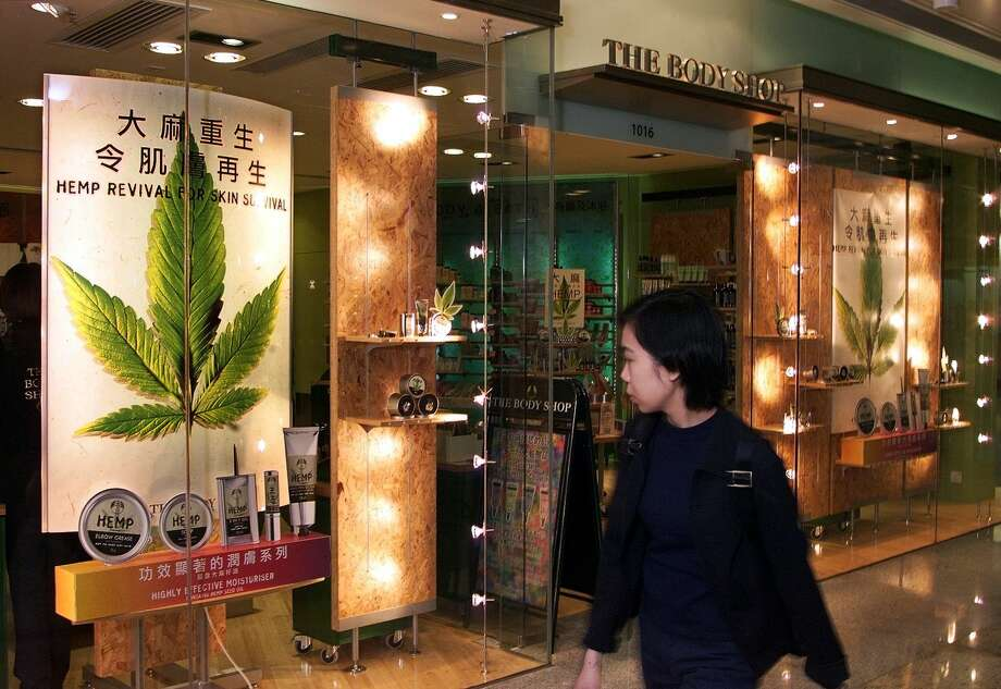 A Hong Kong woman looks at the display window of British-based cosmetic outlet The Body Shop decorated with a cut-out picture of a cannabis leaf on November 2, 1998.  Hong Kong narcotics bureau investigated a range of hemp-based products by the cosmetics company to test whether they contravene drug laws. Photo: MANUEL CENETA, AFP/Getty Images / AFP