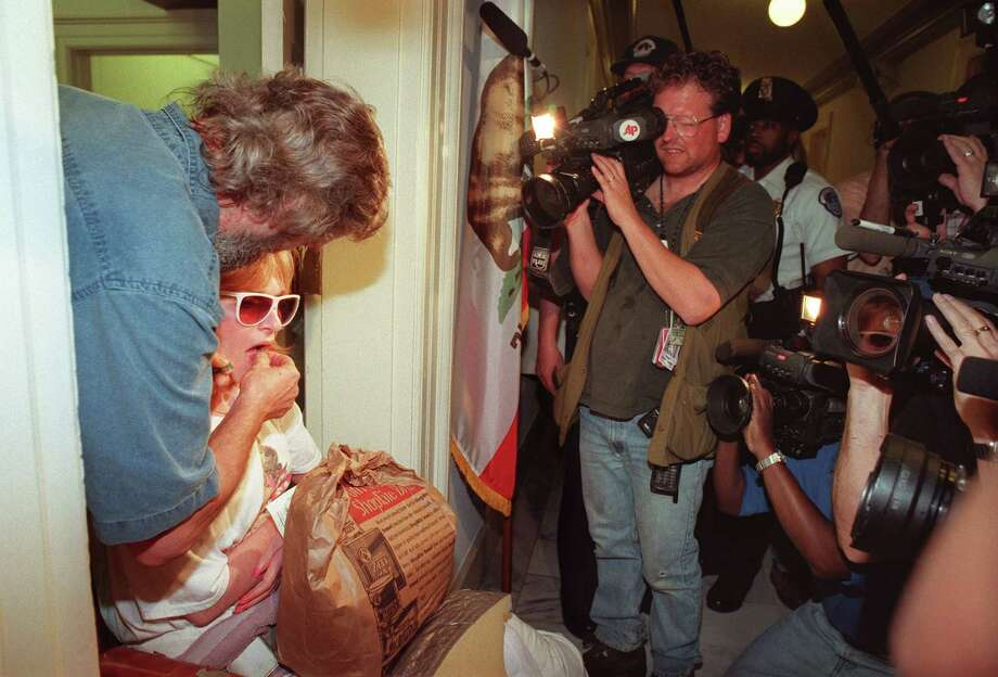 Cheryl Miller from Silverton, N.J., severely disabled by Multiple Sclerosis, is given marijuana to chew by her husband Jim as they participate in a protest against anti-medicinal marijuana legislation, in the doorway of the office of U.S. Rep. Jim Rogan, R-CA, on March 30, 1998, in Washington, D.C. Rogan's office was targeted because he voted for favorable legislation in 1995, citing that a relative found relief by using the drug, and then voted for a House resolution proclaiming opposition to medicinal use of marijuana. Miller was arrested for marijuana possession.  Photo: JOYCE NALTCHAYAN, AFP/Getty Images / AFP