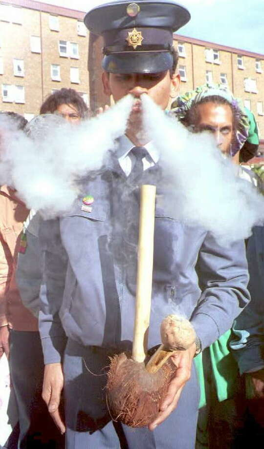 "Police constable Denver Sas smokes a water pipe known as a ""hubbly bubbly"" filled with marijuana on May 11, 1995 before the start of a protest march to legalize the substance in Cape Town, South Africa. Photo: GARY BERNARD, AFP/Getty Images / AFP"
