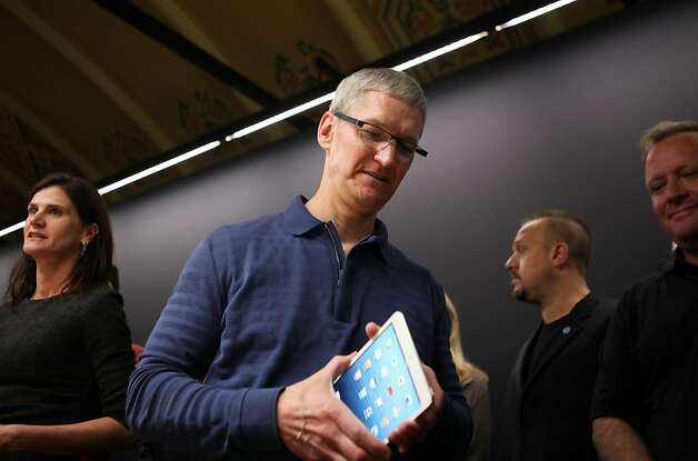 "(FILES)Apple CEO Tim Cook  examines an iPad Mini during Apple's special event at the California Theatre in San Jose, CA in this October 23, 2012 photo.  Apple plans to bring some manufacturing of its computers from China to the United States next year, chief executive Tim Cook said, in a move aimed at sparking more domestic high-tech production. Cook, in two interviews released December 6, 2012, said one line of Mac computers will be made exclusively in the United States, but did not say which one, nor did he say where the manufacturing would be done. The interviews with NBC News, to air later Thursday, and with Bloomberg Businessweek, were the first since Cook took the reins at Apple from Steve Jobs, who died last year from cancer. ""Next year we're going to bring some production to the US,"" Cook told Businessweek. AFP PHOTO/ Kimihiro HoshinoKIMIHIRO HOSHINO/AFP/Getty Images Photo: Kimihiro Hoshino, AFP/Getty Images"