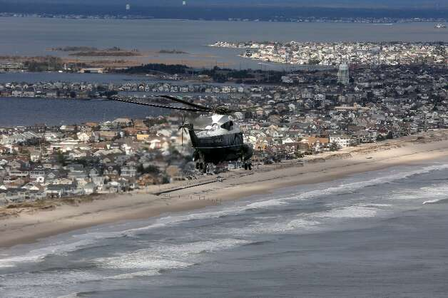 The view of storm damage over the Atlantic Coast from the helicopter following Marine One (C) with US President Barack Obama and Governor Chris Christie as they view the storm damage in Seaside Heights, New Jersey, on October 31, 2012. Americans sifted through the wreckage of superstorm Sandy on Wednesday as millions remained without power. The storm carved a trail of devastation across New York City and New Jersey, killing dozens of people in several states, swamping miles of coastline, and throwing the tied-up White House race into disarray just days before the vote. AFP PHOTO/POOL/Doug MillsDOUG MILLS/AFP/Getty Images Photo: DOUG MILLS, AFP/Getty Images / AFP