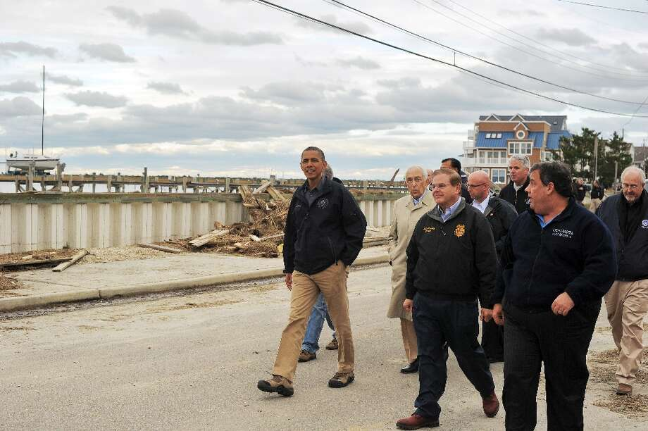 US President Barack Obama (C) and New Jersey governor Chris Christie (R) visits a neighborhood on October 31, 2012 in Brigantine, New Jersey, hit hard by Hurricane Sandy. Americans sifted through the wreckage of superstorm Sandy on Wednesday as millions remained without power. The storm carved a trail of devastation across New York City and New Jersey, killing dozens of people in several states, swamping miles of coastline, and throwing the tied-up White House race into disarray just days before the vote. AFP PHOTO/Jewel SamadJEWEL SAMAD/AFP/Getty Images Photo: JEWEL SAMAD, AFP/Getty Images / AFP