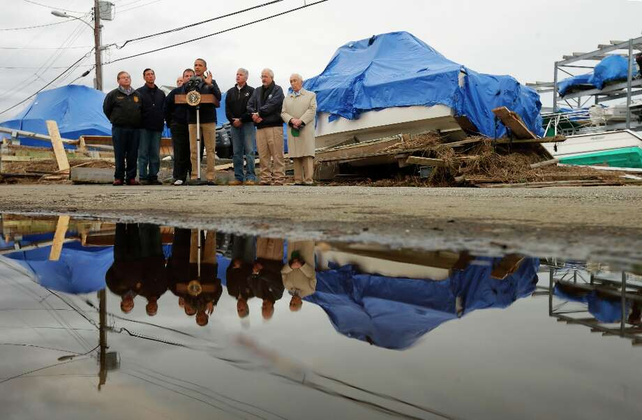 President Barack Obama, center, with New Jersey Gov. Chris Christie, Federal Emergency Management Agency administrator Craig Fugate, and other local and federal officials, speak about the relief efforts causes by the effect of superstorm Sandy, while standing in front of North Point Marina, Wednesday, Oct. 31, 2012, in Brigantine, N.J. (AP Photo/Pablo Martinez Monsivais) Photo: Pablo Martinez Monsivais, Associated Press / AP