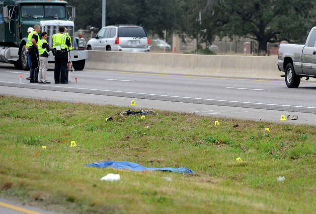 A blue tarp covers the body of a 23-year-old man that Beaumont Police are investigating as a hit and run that occurred on U.S. 69 sometime before 6:30 Thursday morning. The incident occurred just north of the LNVA Canal. Photo taken Thursday, December 06, 2012 Guiseppe Barranco/The Enterprise Photo: Guiseppe Barranco, STAFF PHOTOGRAPHER / The Beaumont Enterprise