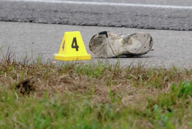 A shoe is tagged with an evidence marker from Thursday morning's possible hit and run that left a 23-year-old man dead. The impact was enough to remove a shoe from the man. Beaumont Police are investigating the incident that occurred on U.S. 69 sometime before 6:30 Thursday morning just north of the LNVA Canal. Photo taken Thursday, December 06, 2012 Guiseppe Barranco/The Enterprise Photo: Guiseppe Barranco, STAFF PHOTOGRAPHER / The Beaumont Enterprise